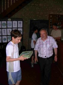 Jérémy reçoit une récompense pour la création du site Web sous l' oeil attentif du Guy Roux des échecs (Serge Dimier)