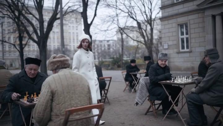 fille rousse avec manteau blanc se baladant parmi des joueurs d'échecs, en Russie, il fait froid dehors
